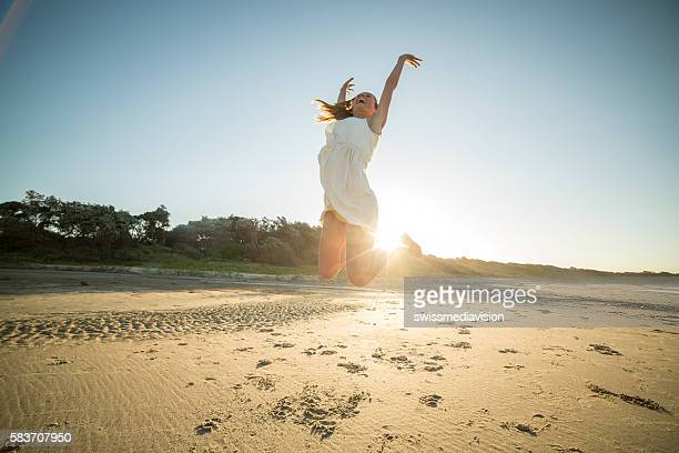 Girl jumps high up in the air on beach-sunset
