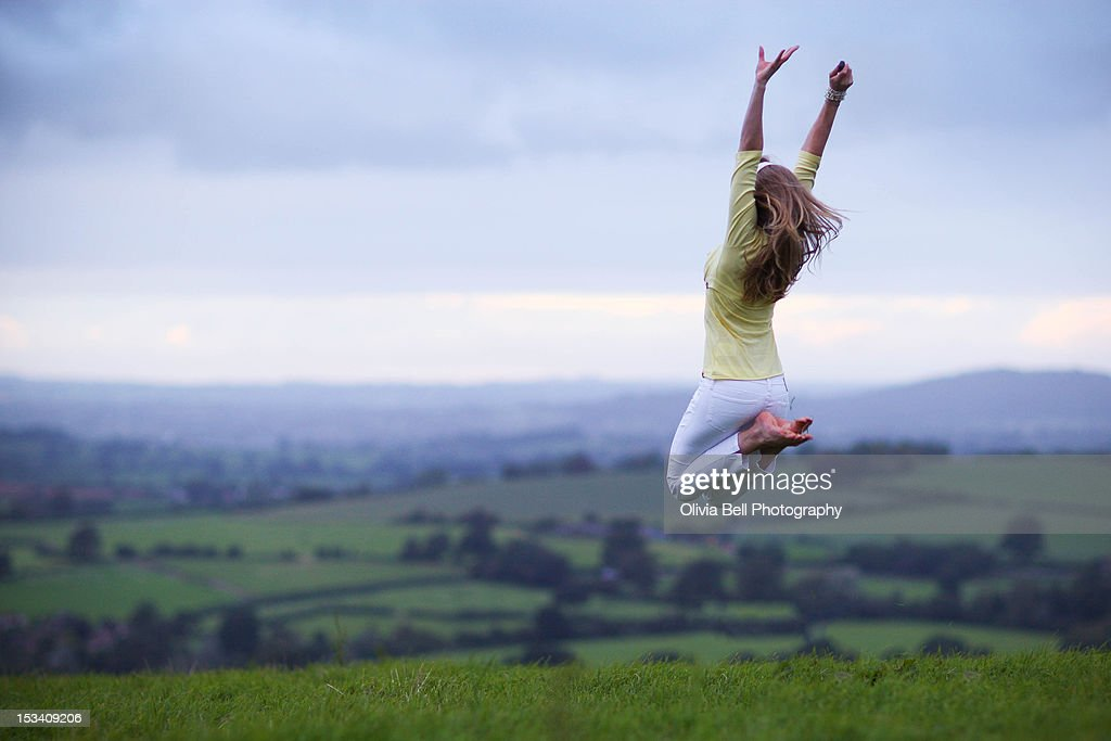 Girl Jumps in Countryside Field : Stock Photo