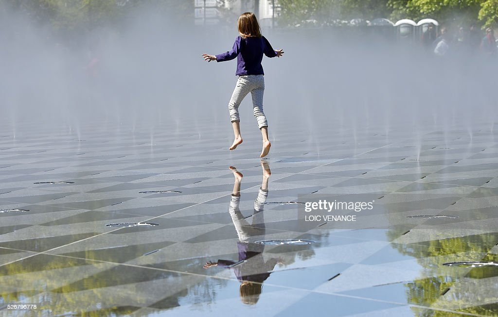 A girl jumps in fountains on the sideline of the traditional May Day rally in Nantes, western France, on May 1, 2016. / AFP / LOIC