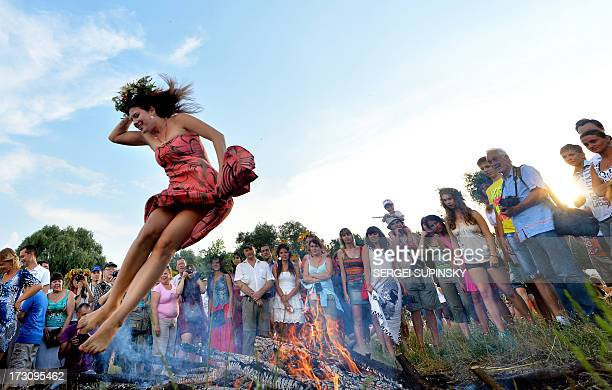A girl jumps over a campfire while celebrating Ivan Kupala Night a traditional Slavic holiday not far from Kiev on July 6 2013 During the celebration...