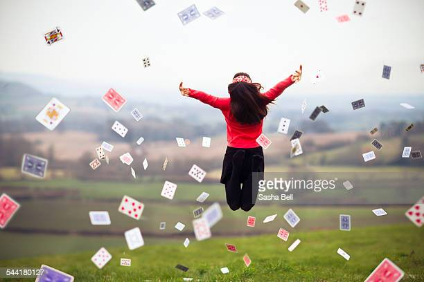 Girl jumps while throwing pack of cards in air