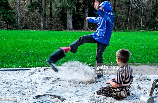 A girl kicks sand out from her boot at Laurel Hill State Park PA.