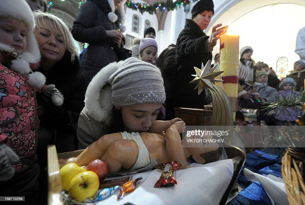 A girl kisses a doll featuring 'Jesus' in a crib during a Christmas service at a Catholic cathedral in Minsk, on December 25, 2012. AFP PHOTO / VIKTOR DRACHEV