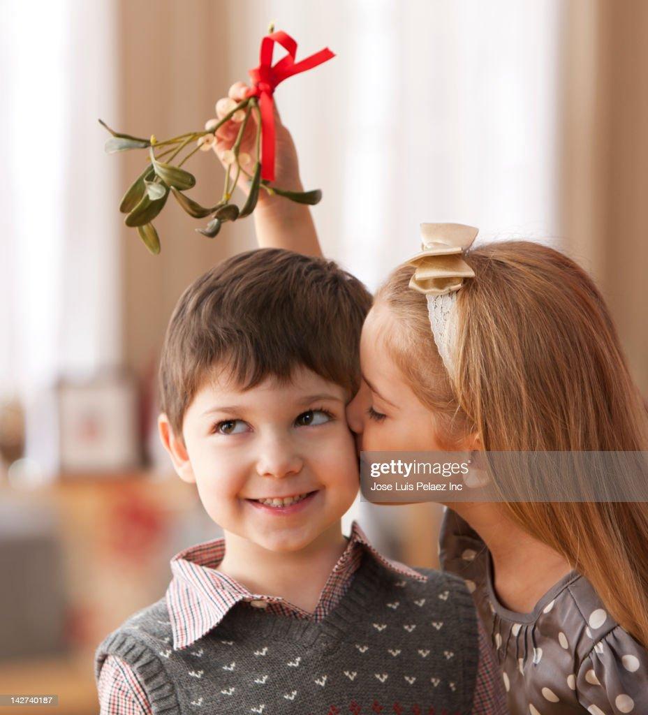 Girl kissing boy underneath mistletoe : Stock Photo