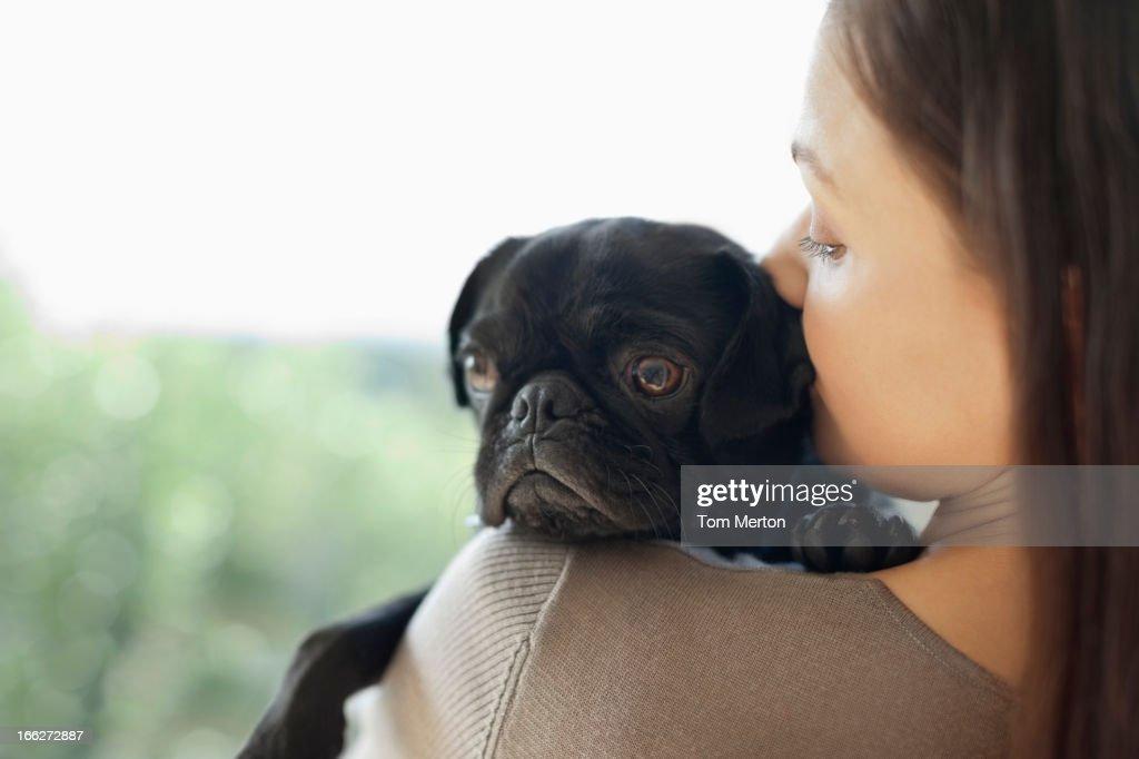 Girl kissing dog on shoulder : Stock Photo