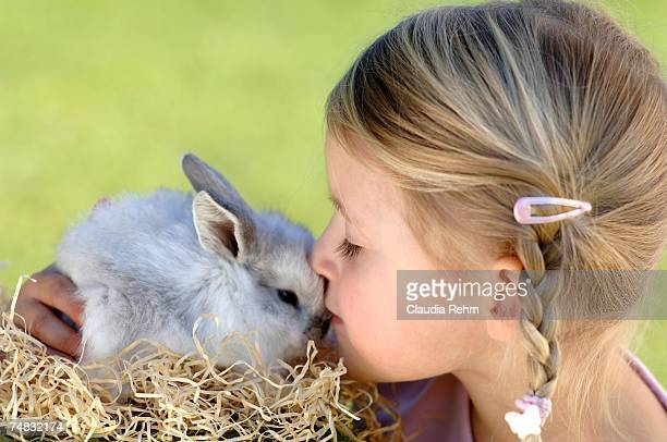 Girl (6-7) kissing Easter bunny, close-up, side view