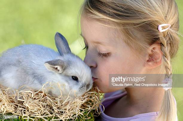 'Girl kissing easter bunny, close-up, portrait'