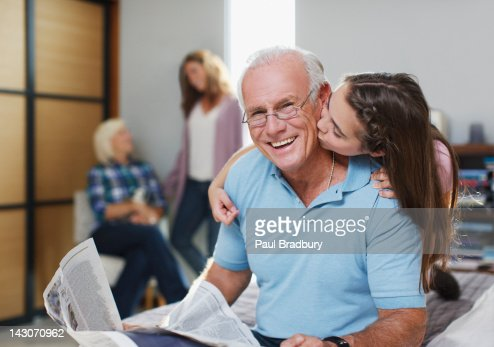 Girl kissing grandfather in home : Stockfoto