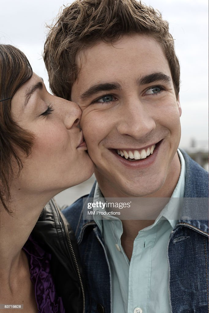 Girl kissing guy on the cheek : Stock Photo