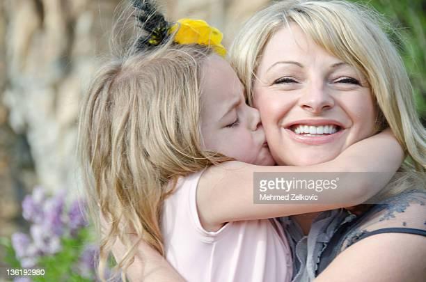 Girl kissing her mom