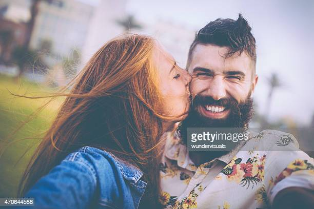 Girl kissing her smiling hipster boyfriend on his cheek