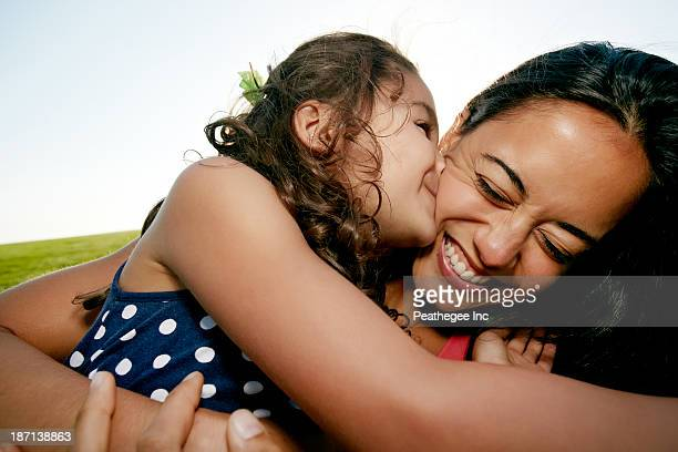 Girl kissing mother on cheek