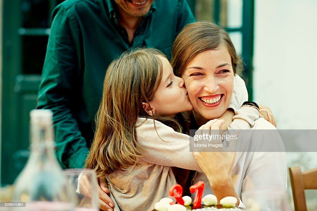 Girl kissing mother while celebrating birthday