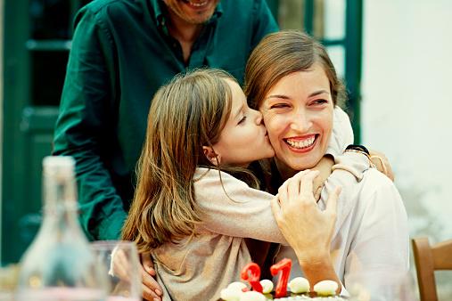 Girl kissing mother while celebrating birthday