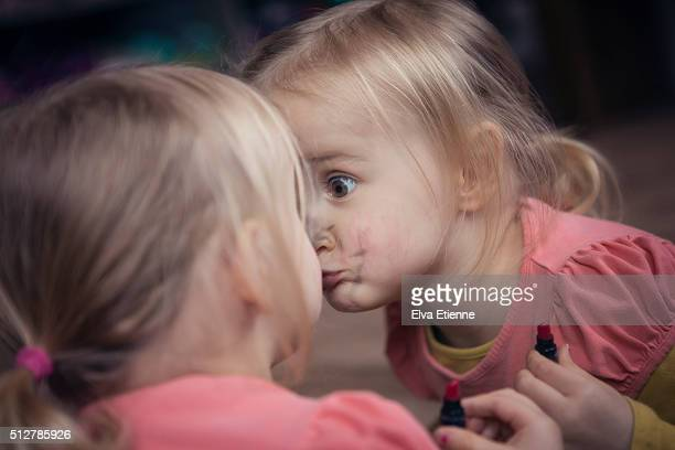 Girl (3-4) kissing reflection in mirror