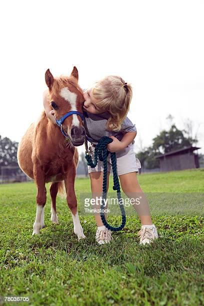 Girl kissing Shetland pony