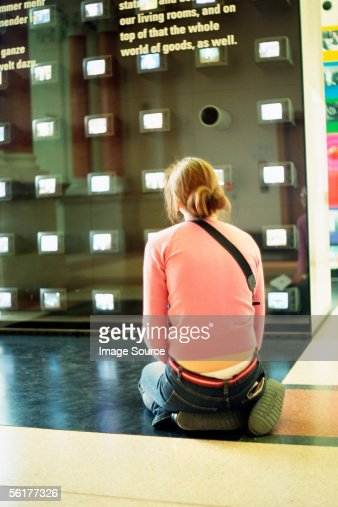 Girl kneeling in art gallery : Stock Photo