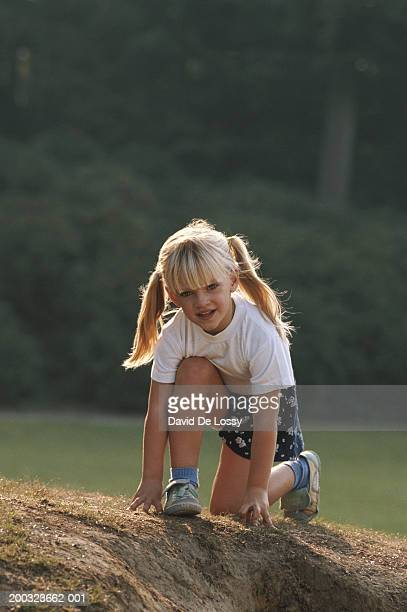 Girl (4-5) kneeling in garden