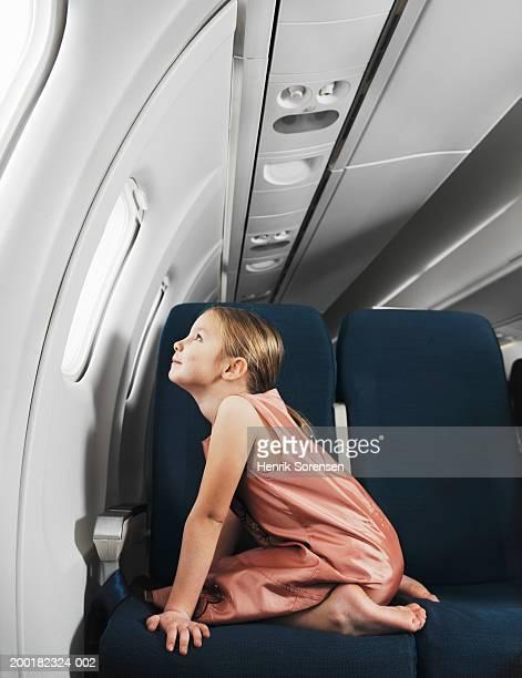 Girl (5-7) kneeling on aeroplane seat looking out window