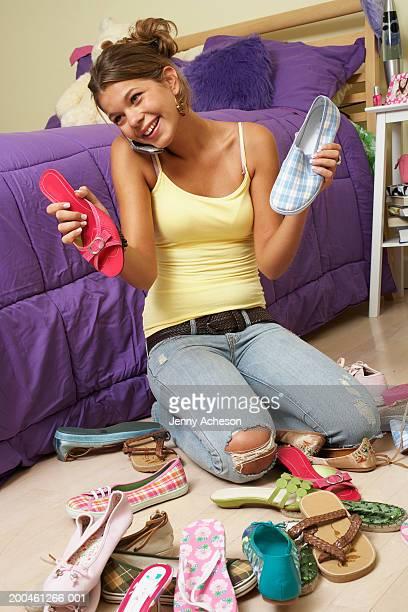 Girl (13-15) kneeling on bedroom floor by piled shoes, using mobile