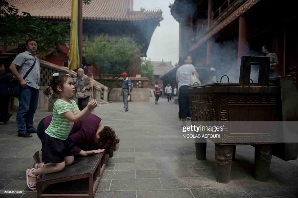 A girl knees and holds incense sticks inside the Lama temple in in Beijing on May 25, 2016. / AFP / NICOLAS