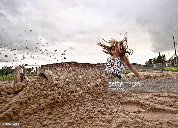 A girl landing in a sandy long jump pit