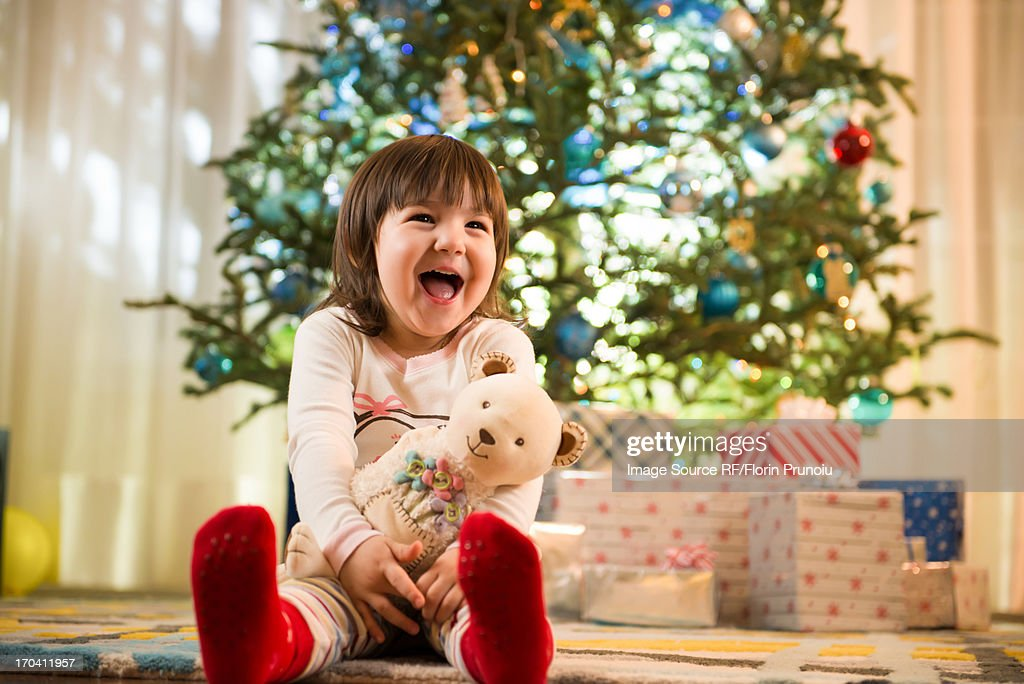 Girl laughing by Christmas tree : Stock Photo