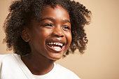 Girl (6-7) laughing, close-up, studio shot
