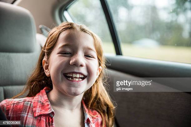 Girl (7) laughing in backseat of car