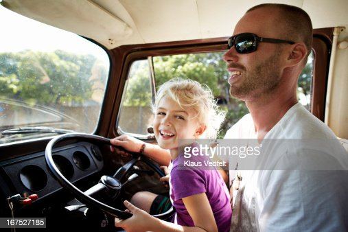 Girl laughing steering a car with her father : Stock Photo