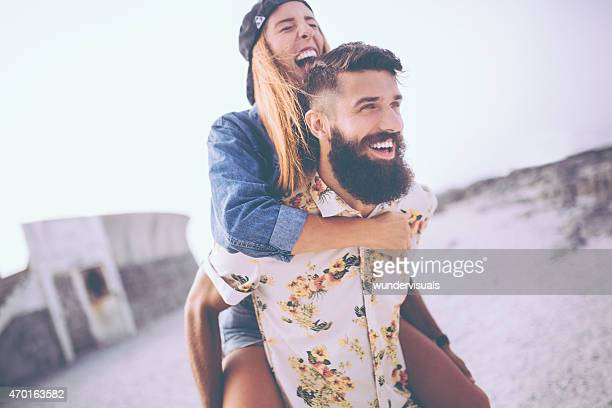 Girl laughing while hipster boyfriend piggybacks her at the beac