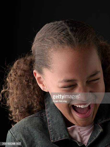 Girl (10-12) laughing with eyes closed, close-up
