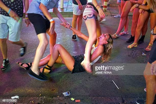 A girl laughs as she sits on the pavement in Punta Ballena street in Magaluf holiday resort in Calvia on the Spanish Mallorca Island on July 19 2014...