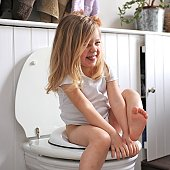 Girl laughs while sitting on loo