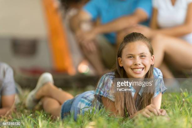 Girl laying in grass outside tent