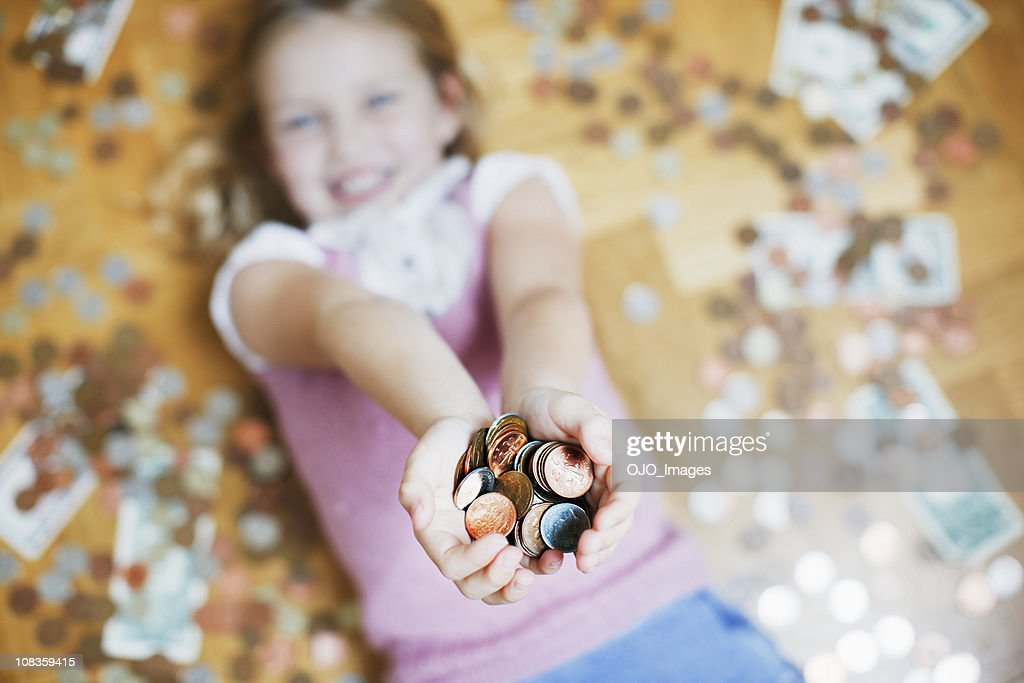 Girl laying on floor holding handful of coins : Stock Photo