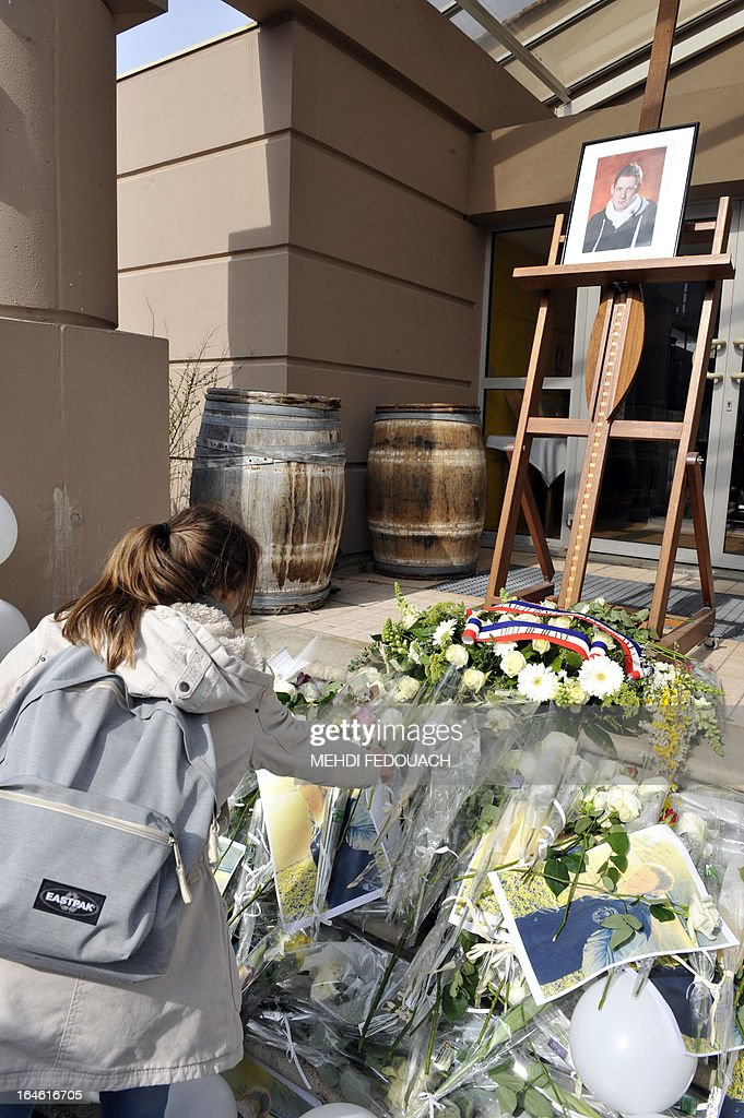 A girl lays a flower on March 25, 2013 in front of a portrait of Sylvain, a 15-year-old schoolboy stabbed on March 19 by a 19-year-old comrade in a classroom of the Estuaire college in Blaye, southwestern France.