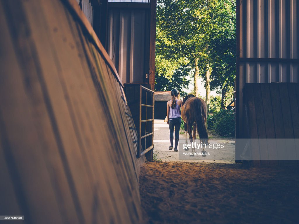 Girl leading her horse out of stables with vintage feel : Stock Photo