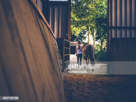 Girl leading her horse out of stables with vintage feel