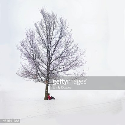 Girl leaning against a tree in the snow