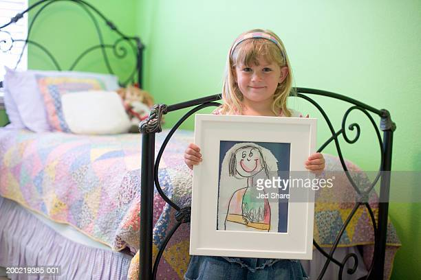 Girl (4-6) leaning against bed, holding drawing, portrait