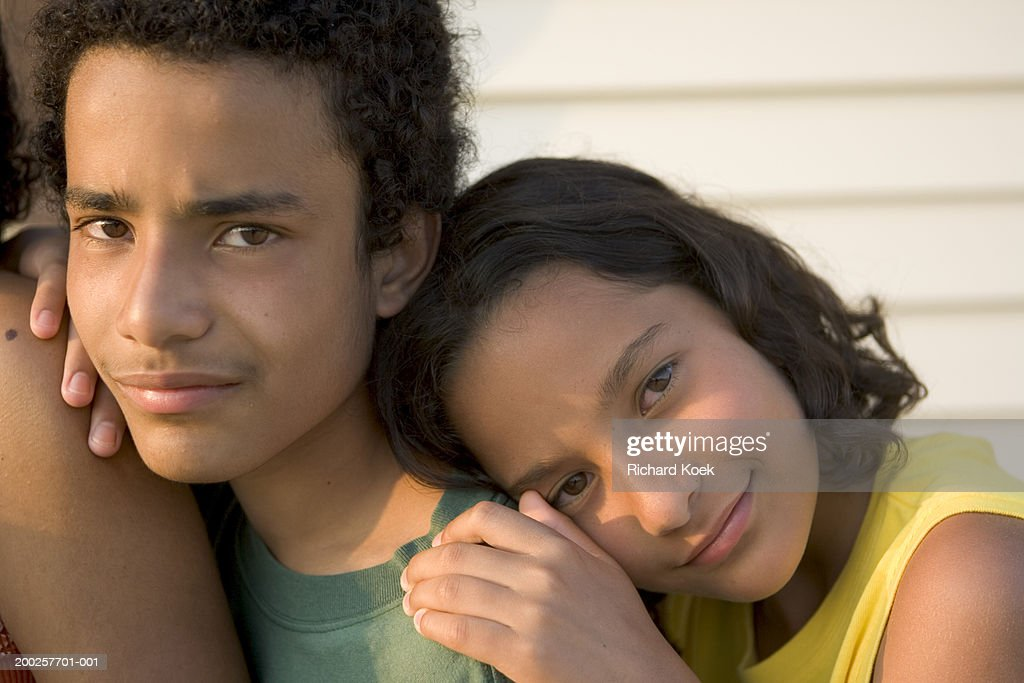 Girl (10-12) leaning against teenage brother's (13-15) shoulder : Stock Photo