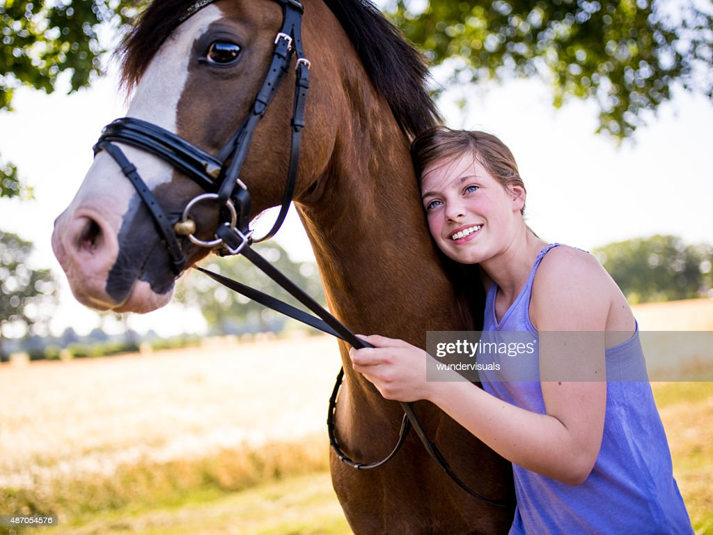 Girl leaning lovingly against her beautiful brown horse
