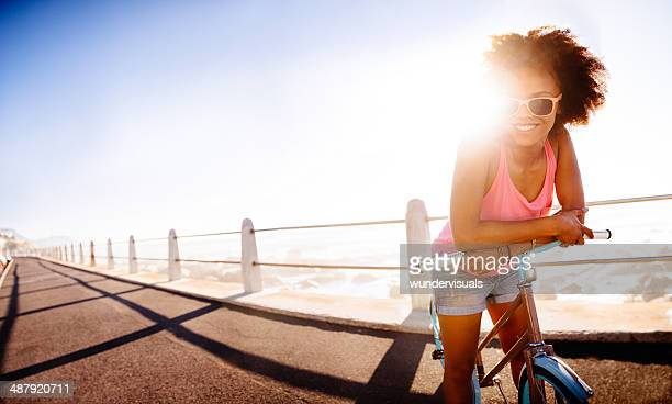 Girl leaning on bike near seaside