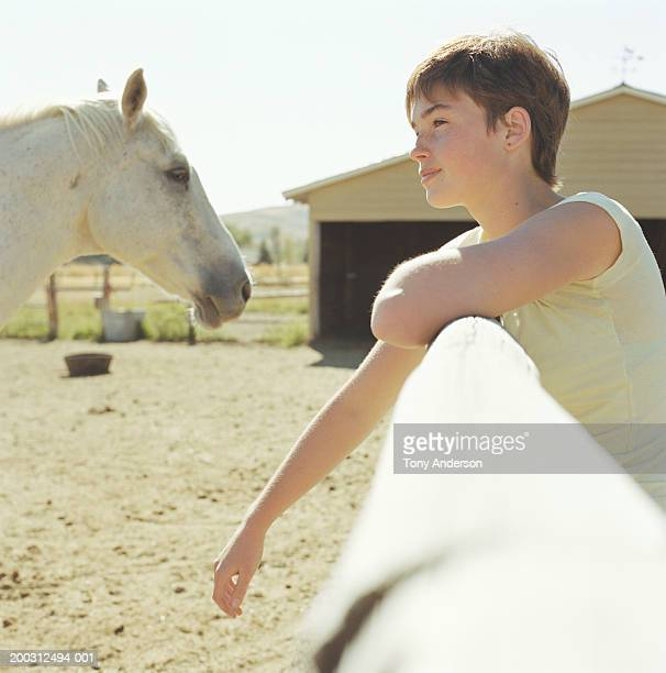 Girl (11-13) leaning on corral fence, side view