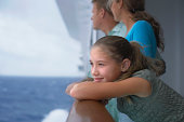 Girl (10-12) leaning on rail of cruise ship, parents in background