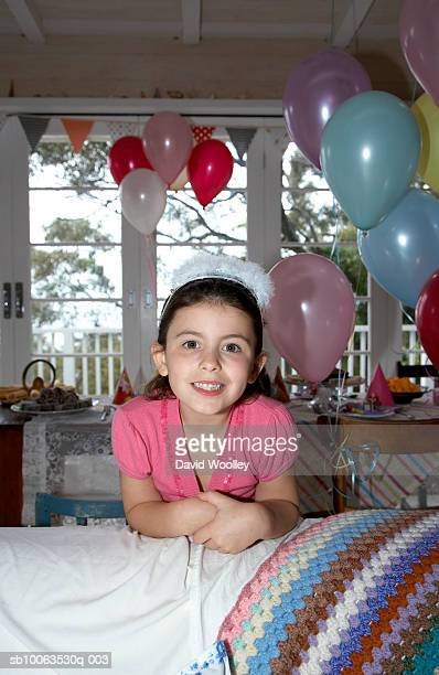 Girl (6-7) leaning on sofa, smiling, portrait