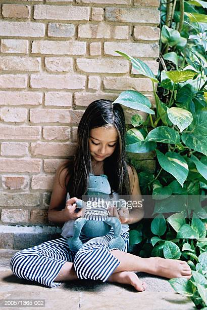 Girl (10-11) leaning on wall playing with soft toy