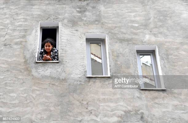 A girl leans over the window of a building on October 4 2017 in the locality of Zarzouna near Bizerte north of Tunis near the family house of...