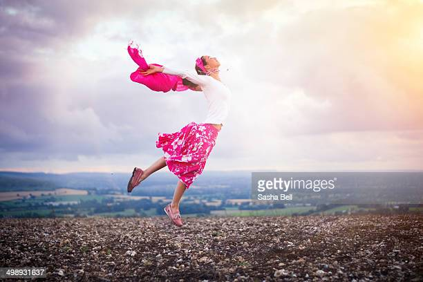 Girl Leaping in Ploughed Field at Sunset